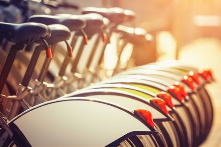 Closeup of bicycles at rental station at sunset