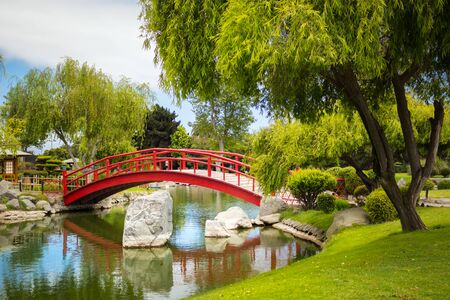 Beautiful red bridge under pond in japanese garden in La Serena, Chile