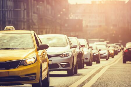 A lot of cars standing in a queue in city center at sunset Фото со стока