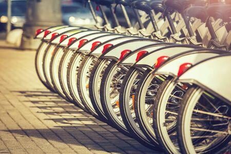 Wheels of bicycles at rental station at sunset
