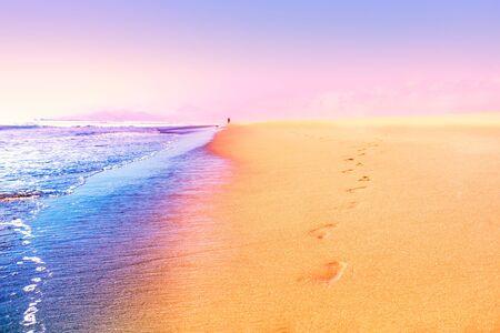 Footprints on the sand near the sea waves at sunset Фото со стока