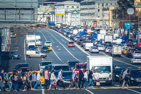 MOSCOW - AUGUST 19, 2016: Group of pedestrians cross Sadovaya-Spasskaya street while cars turn left. This avenue is a part of the Garden Ring road