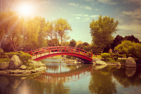 Japanese garden with beautiful red bridge and reflections in the pond at sunset in La Serena, Chile