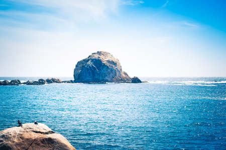 Pacific ocean with rocky island near Algarrobo in Chile