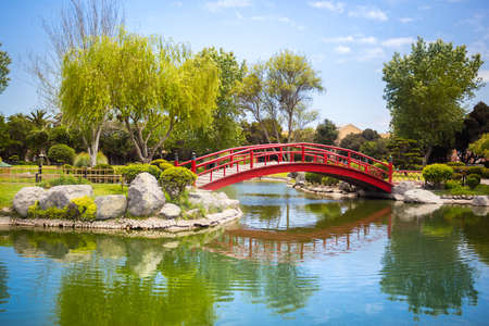Japanese garden with beautiful red bridge and reflections in the pond in La Serena, Chile Фото со стока