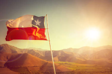 Chilean flag with mountains on the background at sunset