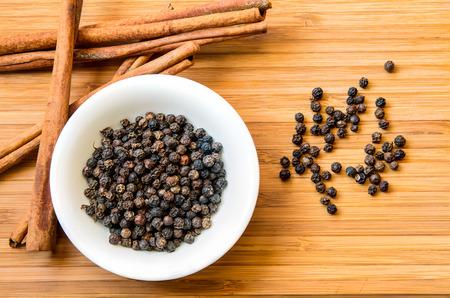 black pepper: Black pepper in white dish and cinnamon on wood floor background