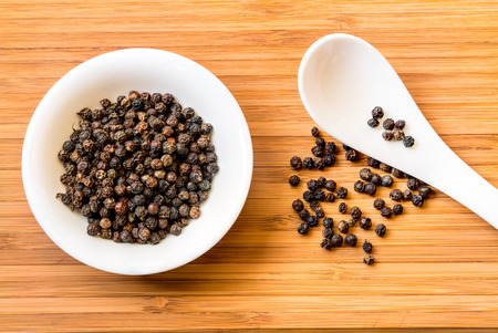 flavorings: Black pepper in white dish and spoon on the wood floor