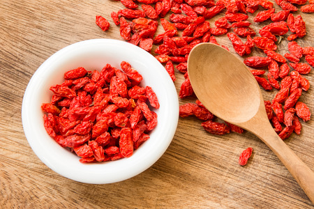 goji berry: Goji berry on white dish with wood spoon on the wood floor