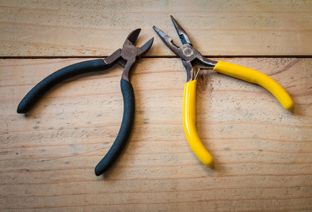 wirecutters: Closeup of the old pliers and wirecutters on wood background Stock Photo