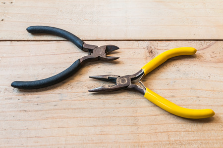 wirecutters: Old wirecutters and  pliers on the wood background Stock Photo