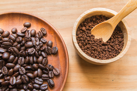 instant coffee: Coffee beans on wood dish with instant coffee in wood bowl