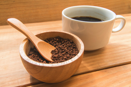 instant coffee: Instant coffee  in the wood bowl with white cup of coffee  focus at instant coffee