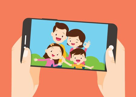 hand hold smartphone with Happy family selfie photo on smartphone display. Selfie photo with Mother, father, son, daughter.
