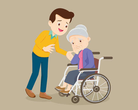 elderly woman sit in a wheelchair and the son tenderly puts hands on her shoulders. Man cares for mother.Careful caregiver taking care of the patient man consoling Grandmother
