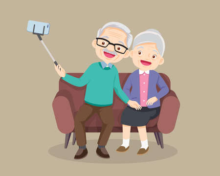 elderly couple seat on sofa and making photo together on mobile phone with selfie stick.Old man and woman take selfie on smartphone