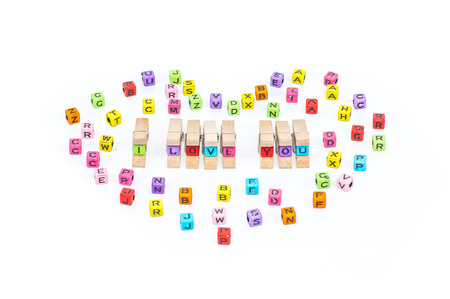 sentiment: Wooden clamps have Message I love you spelled in plastic blocks with over white background and other alphabet