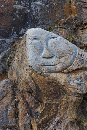 incensed: Face carved on stone The diversity underpinsm sad, angry, happy as public art in the city, walking along the street Qaqortoq Greenland.
