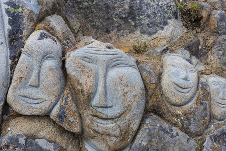 gratified: Face carved on stone The diversity underpinsm sad, angry, happy as public art in the city, walking along the street Qaqortoq Greenland.