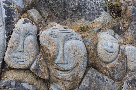 Visage sculpté sur la pierre La diversité underpins'm triste, en colère, heureux comme art public dans la ville, marchant le long de la rue Qaqortoq Groenland.