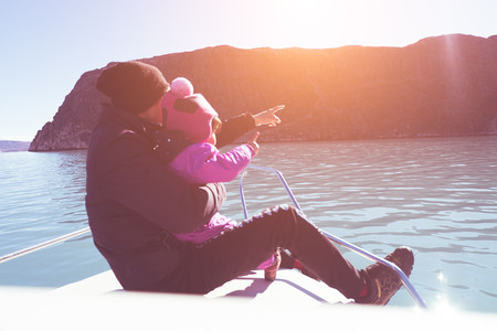 finger bow: Father with daughter on the bow of the ship. hold daughter with hand and point finger on sunset background. lover and family concept mean love from father