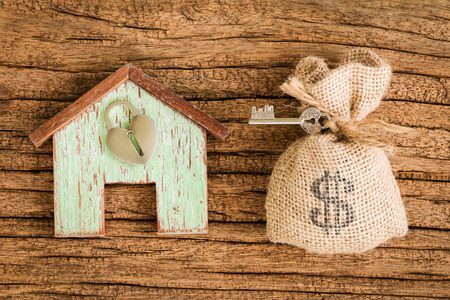 lend: Home model and a money and key put on the wooden vintage background, Buying a new house and real estate concept.