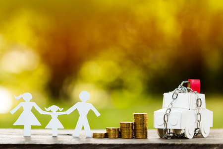 Een familie- en automodel met veiligheid en het vergrendelen en stapelen van gouden munten in openbaar park, waardoor geld wordt bespaard voor het eigendoms- en eigendombeschermingsconcept.