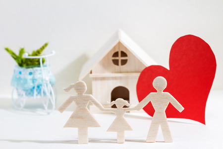 A family and home with model, red heart paper on background for buy a new real estate or loan for planned investment in the future concept.