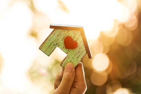 Femme main tenant un modèle de maison avec un coeur rouge dans la lumière du soleil dans le parc public, Prêts pour l'immobilier ou économiser de l'argent pour acheter une nouvelle maison à la famille dans le futur concept.