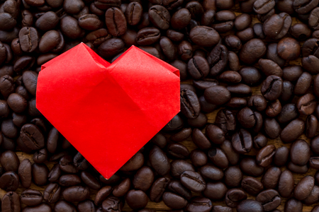 A red paper heart placed on roasted coffee beans, For owner cafe with love concept. Stock Photo