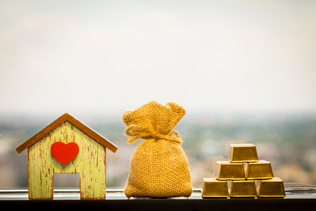 Home with red heart and a money bag and a gold bar to grow up put on the window sill in office, Loans for real estate or save money for buy a new house in the future concept. 免版税图像
