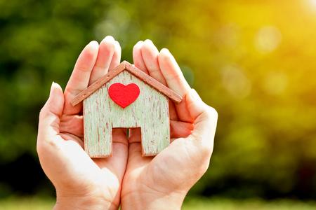 La mano de la mujer que sostiene un modelo casero pega un corazón rojo en la luz del sol en el parque público, préstamos para bienes inmuebles o ahorra dinero para comprar una nueva casa para la familia en el concepto futuro.