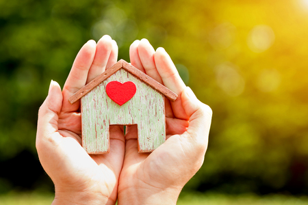 Woman hand holding a home model stick a red heart in the sunlight in the public park, Loans for real estate or save money to buy a new house for family in the future concept.