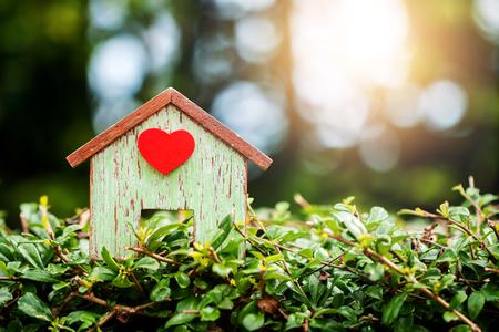 Vara de madeira em casa um coração vermelho colocar no chão da grama no parque público, empréstimos para imóveis ou economizar dinheiro para comprar uma nova casa para a família no futuro conceito.