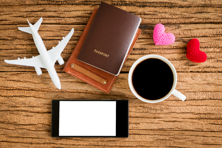 Passport and black coffee and a wallet and a plane model and red heart and smartphone with copy space for ad text put on the wood texture for travel planning and advertising business concept. Stock Photo