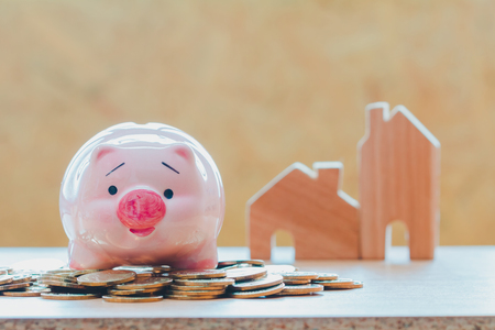 Piggy bank put on the stacking coins on home for family background, saving money for buy a new real estate or loan for planned investment in the future concept.