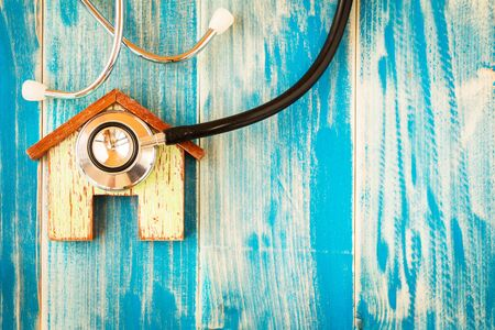 Home and stethoscope put on the vintage blue background, Loan for buy a new house or real estate concept. Stockfoto