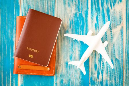 Passport and a brown leather wallets a plane model put on the vintage blue background for travel planning concept. Reklamní fotografie