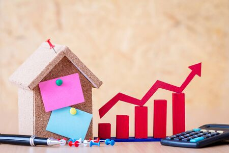 Home model and mix color reminder paperpost note for write text and pin and red arrow bar graph with growing value and calculator put on the desk, loan for buy a house or real estate concept. Stockfoto