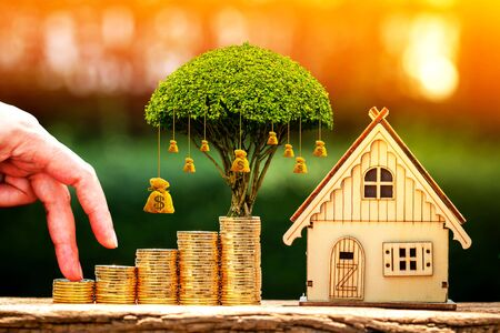 Close up of hand with climb up on a stacking gold coins and a home model as destinations for growing and money bag, Loan or saving for real estate or buy a new house in the future concept. Stockfoto