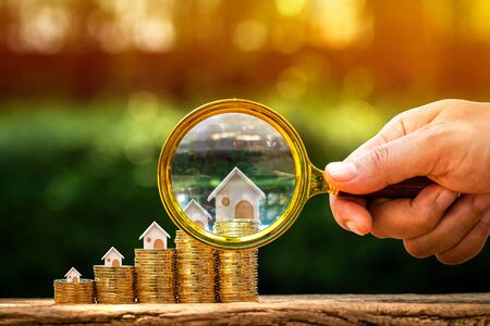 Investor hand hold a magnifier with searching for new home and a stack gold coin growing in the public park, Loan for real estate or saving money for buy a new house to family in the future concept. Stock fotó