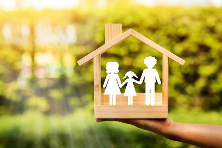 Woman hand holding a wooden home with happy family of paper art is placed inside on nature bokeh in the public park, The saving money for house or real estate owner in the future concept.