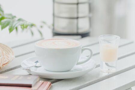 Shot de café y leche condensada y pasaporte y una billetera y un modelo de avión puestos sobre la mesa en el café para el concepto de planificación de viajes.