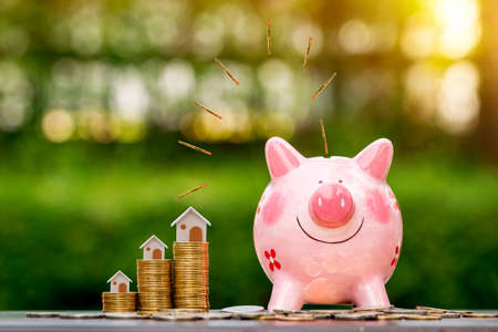 Piggy bank and coin drop on the top with working capital management and home model is destination put on the wood in the public park, Loan and business investment with real estate for future concept.