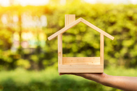 Woman hand holding a wooden home model on the sunlight in the public park, Loan for real estate or save money for buy a new house to family in the future concept.