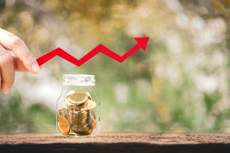 Woman hand hold a red arrow graph with growing value to the bottle bank with gold coins inside put on the wood and sunlight in public park, Saving money and loan for business investment concept.