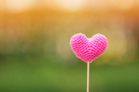 The heart yarn pastel color pink on bokeh sunlight in the public park, for give supporting when people get who lack of desire with love and Valentine day concept.