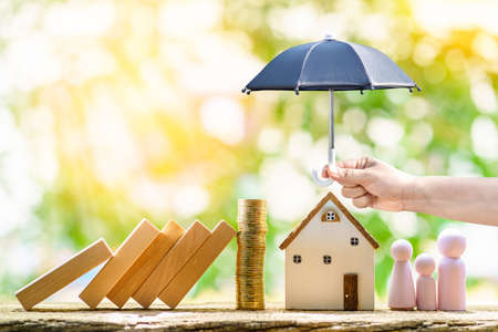 Collect gold coin and woman hand hold open the black umbrella for protect the home and family from hazard falling wood block in the public park, Saving money for buy insurance of real estate concept.