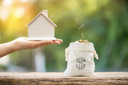 Businessman hand hold the house and gold coin drop to the money bag with working capital management in the public park, Saving money for real estate and loan for buy home for investment concept.