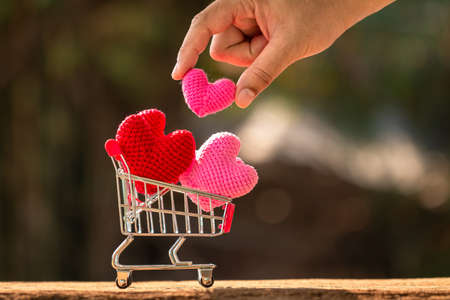 Man hand hold a heart cumulative in the shopping cart  put on the wood on beautiful bokeh background, Buy insurance or for give supporting when people get who lack of desire with love concept.